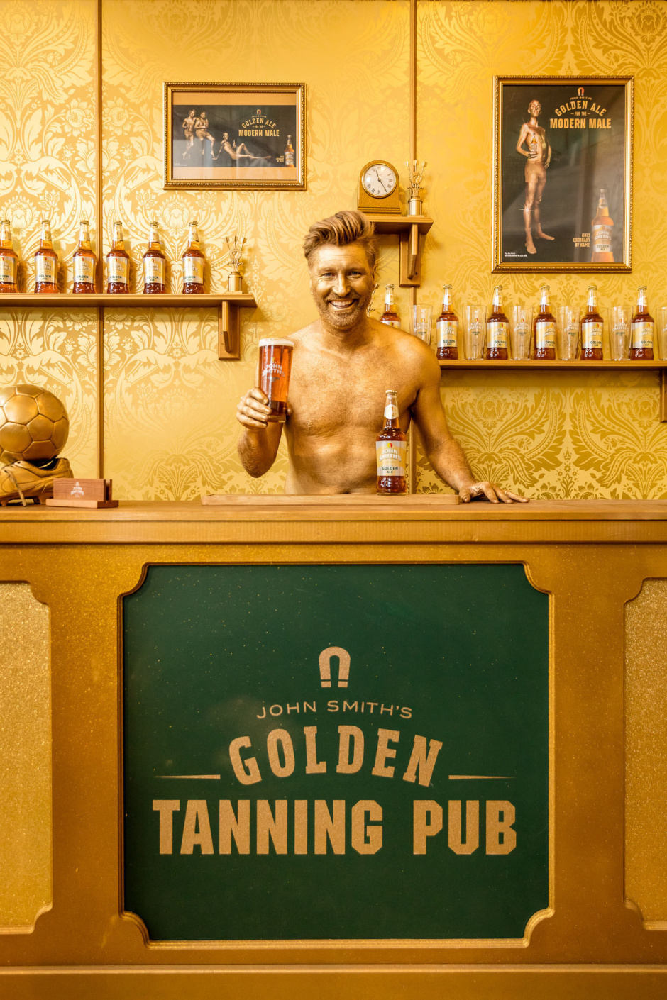 Golden Ale for the Modern Male: Former footballer Robbie Savage is pictured serving pints and sporting a dazzling golden spray tan at the launch of the John Smith's Golden Tanning Pub in London. The entirely gold pub-come-tanning salon has been created to mark the launch of the new John Smith's Golden Ale advertising campaign and opens its doors to the public on Wednesday 27th April.