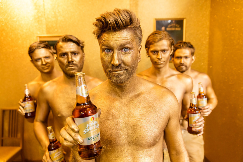 Golden Ale for the Modern Male: Former footballer Robbie Savage is pictured sporting a dazzling golden spray tan at the launch of the John Smith's Golden Tanning Pub in London. The entirely gold pub-come-tanning salon has been created to mark the launch of the new John Smith's Golden Ale advertising campaign and opens its doors to the public on Wednesday 27th April.