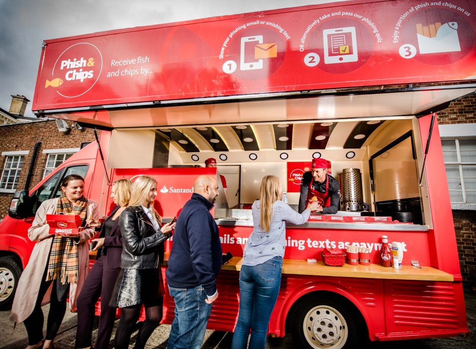 FREE FOR EDITORIAL USE ONLY, NOT FOR FURTHER SYNDICATION A queue forms outside Santander's fish and chip van as Jenson Button serves the public in exchange for phishing emails and smishing texts. Byline John Nguyen/Santander