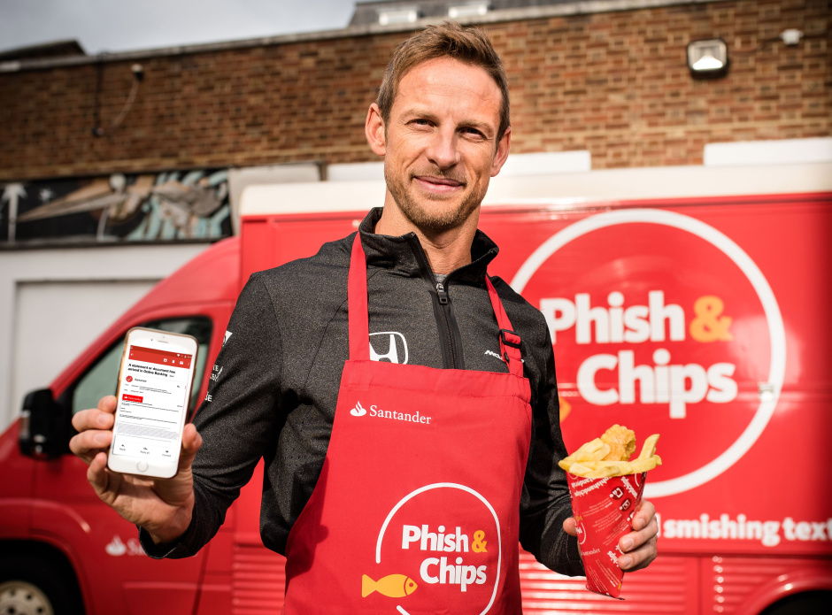 FREE FOR EDITORIAL USE ONLY, NOT FOR FURTHER SYNDICATION Jenson Button stands outside Santander's fish and chip van where he has been serving fish and chips to the public in exchange for phishing emails and smishing texts. Byline John Nguyen/Santander