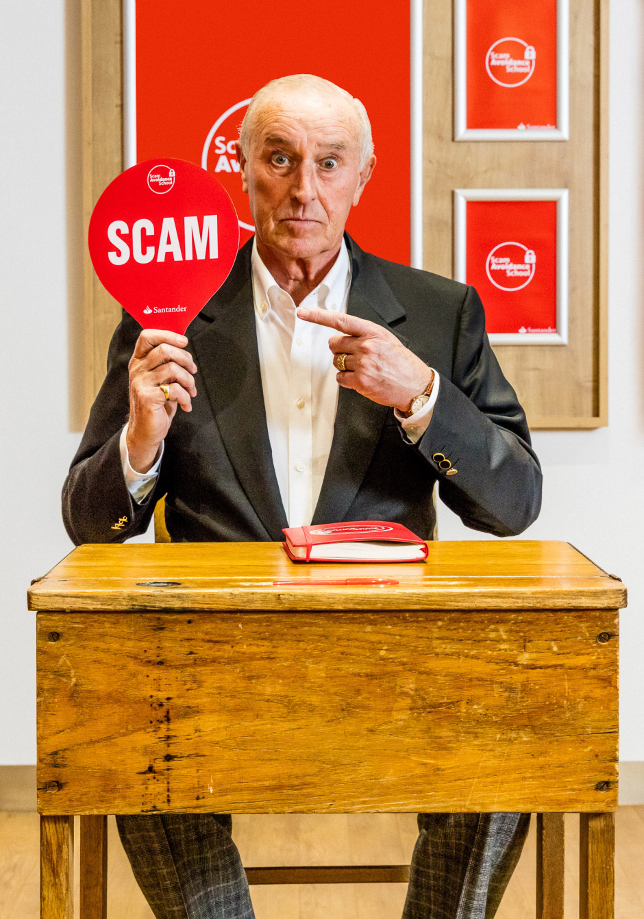 Len Goodman joins the SAS: Former Strictly Come Dancing judge Len Goodman has become the first graduate of the Scam Avoidance School - a new nationwide initiative by Santander for the over 60s offering free scam avoidance training. The SAS will run in all 806 Santander branches from 19 - 23 March. This picture: A 10 for Len as he correctly spots a scam during the Scam Avoidance School. For further information please contact Cow PR on 020 7234 9150  or santander@cowpr.com PR Handout - free for editorial usage.  Copyright: © Santander